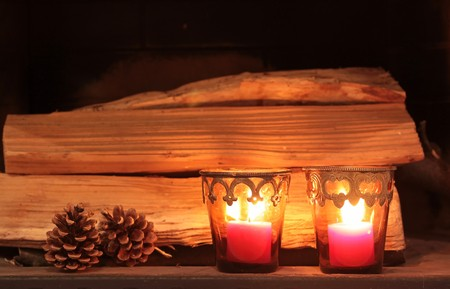 Burning candles as Christmas decoration in front of firewood photo