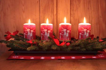 �advent: 4 De velas de Adviento, quema en frente de un muro de madera  Foto de archivo