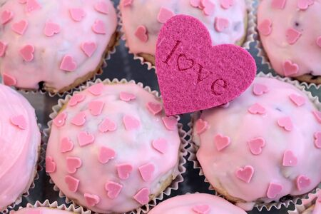 Muffins with pink icing and a shape Heart Love photo