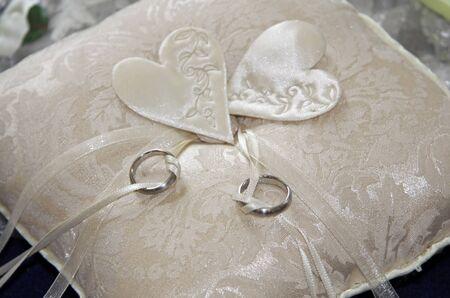 verlobt: Two Wedding Rings auf einem Beige Kissen