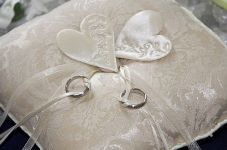 engaged: Two wedding rings on a beige pillow