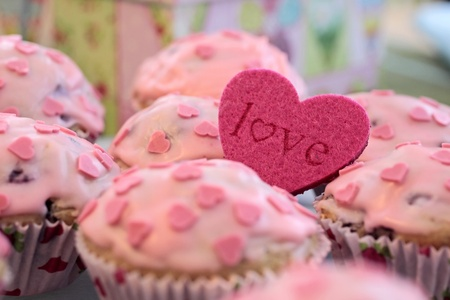 Muffins with pink icing and a heart shape Love photo