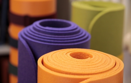 mats: Colorful yoga mats rolled up in a yoga school