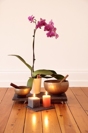 singing bowl: Orchid, candele, orchidee e campane tibetane come decorazione in una sala yoga Archivio Fotografico