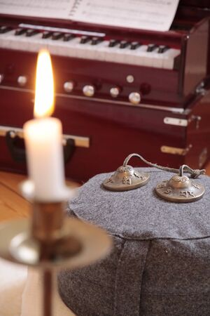 singing bowls: Candle, harmonium and cymbal as decoration in a yoga room