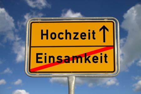 ortseingangsschild: Die deutsche Zeichen Einsamkeit und Hochzeit mit blauem Himmel und weißen Wolken