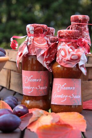 harvest time: Glasses with homemade sauce and autumn decoration Stock Photo
