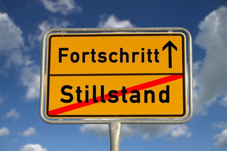 downtime: German road sign stagnancy and progress with blue sky and white clouds