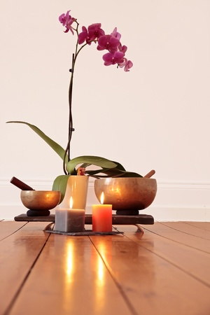 Orchid, orchid candles and singing bowl as a decoration in a yoga room