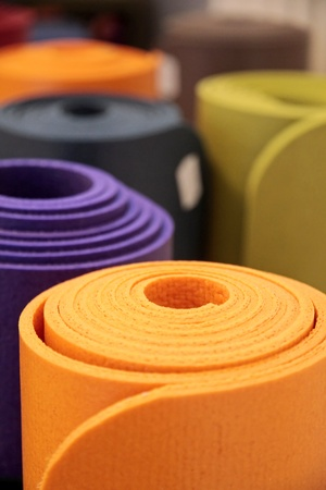 Colorful yoga mats rolled up in a yoga school
