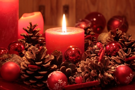 christmas atmosphere: Advent  wreath with pine cones  and  burning candle