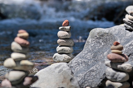 Cairn with red stone by the stream in the Tongariro National Park, Manawatu-Wanganui, New Zealand photo