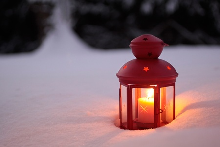 Burning lantern in the snow at twilight