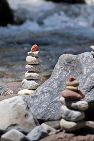 rock pile: Cairn with red stone by the stream in the Tongariro National Park, Manawatu-Wanganui, New Zealand Stock Photo