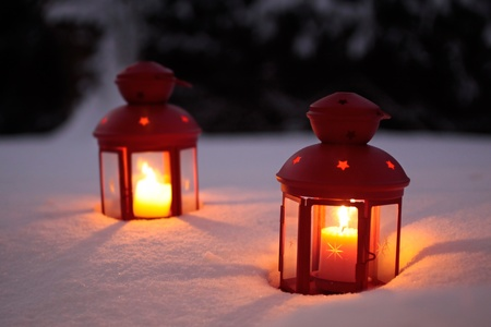 mood: Two burning lanterns in the snow at twilight