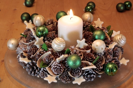 Advent  wreath with pine cones  and  burning candle photo