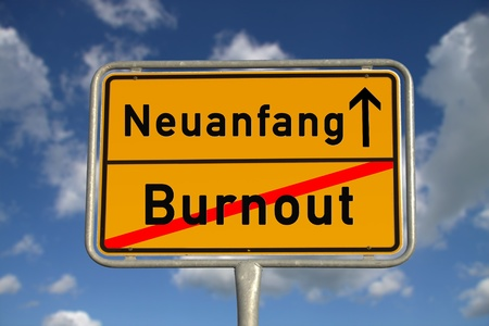 burdened: German road sign  burnout and new beginning with blue sky and white clouds Stock Photo