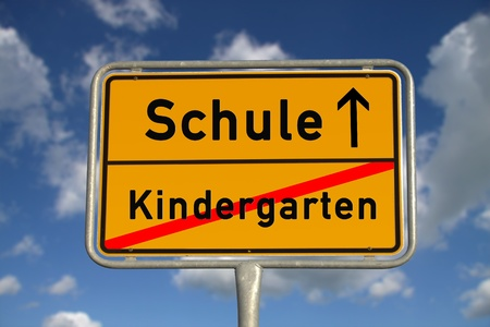 German road sign kindergarten and school with blue sky and white clouds