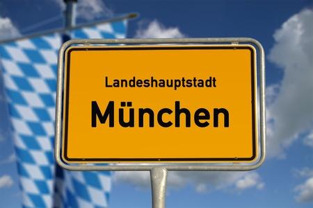 ortseingangsschild: Deutsch Straßenschild München, Bayern mit Fahne, blauer Himmel und weiße Wolken