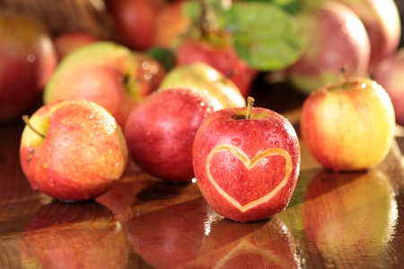 love proof: Wet apples on wooden desk with heart shape