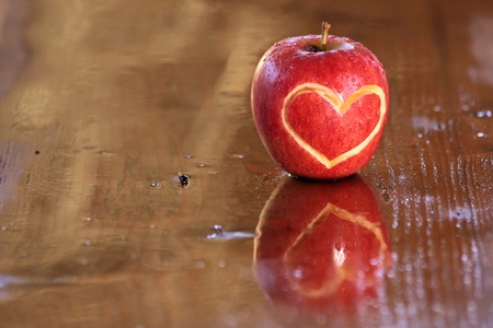 love proof: Red wet apple with heart shape on wooden desk Stock Photo