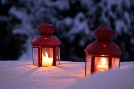 Two burning lanterns in the snow at twilight