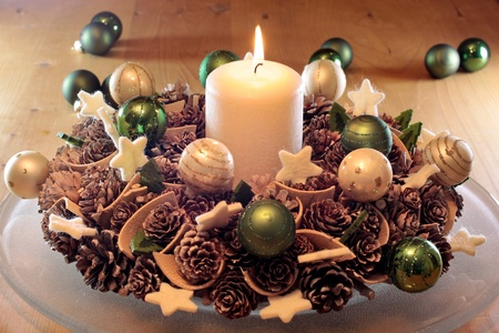 Advent  wreath with pine cones  and  burning candle