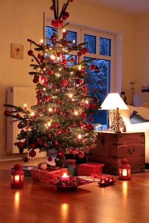 Illuminated Christmas tree in German home with candlelights photo