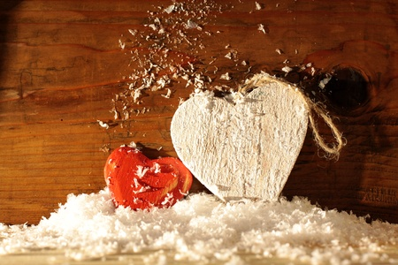 love proof: Two wooden hearts in snow in front of wooden wall