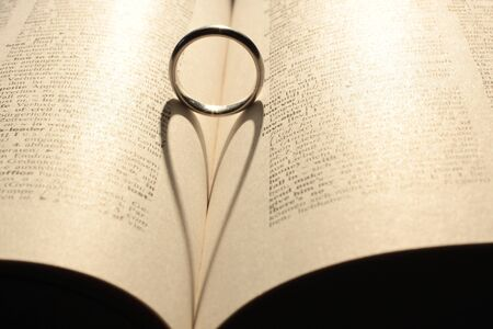 love proof: Heart shadow from wedding ring on book
