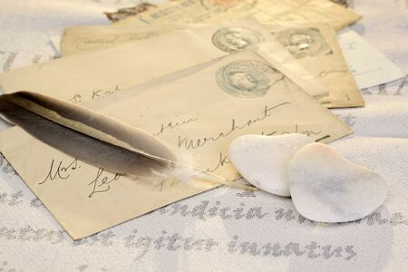 love proof: Two stone hearts with feather and old letters Stock Photo