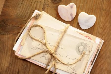 carta de amor: Corazones de piedra con viejas cartas atadas en el escritorio de madera