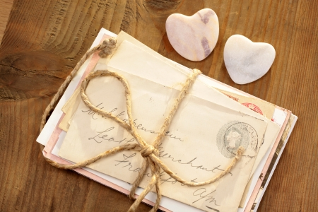 bundle of letters: Stone hearts with old tied letters on wooden desk
