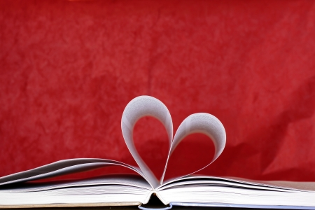 Heart shape of book pages against a red background
