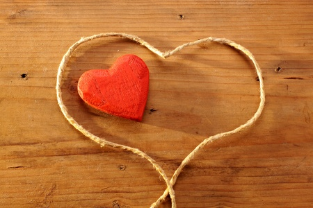 love proof: Red wooden heart with heart rope on desk