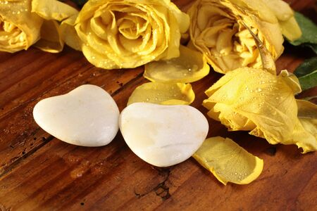 love proof: Two stone hearts and yellow roses on wooden desk