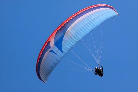 parapente: Paraglider in blauwe hemel bij Bobs Peak, Queentown, Otago, Zuid eiland, Nieuw-Zeeland Stockfoto