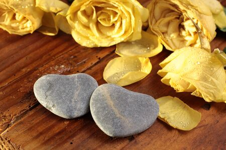 love proof: Stone hearts with yellow roses on wooden desk