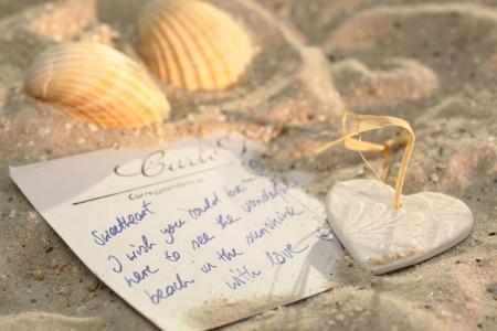 caracolas de mar: Corazón con la tarjeta postal y conchas de mar en la playa Foto de archivo