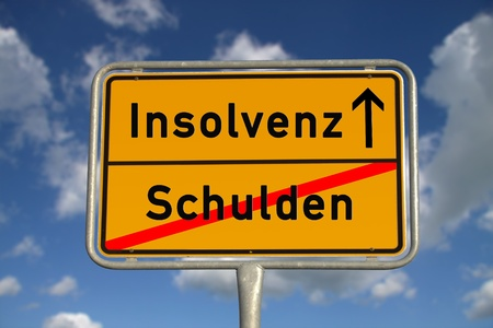 ortsschild: German road sign debt  and bankruptcy with blue sky and white clouds