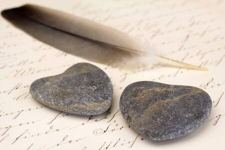 Two stone hearts with feather and old letter Stock Photo - 13779814