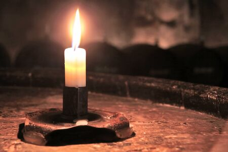 candle light: Burning candle in an old wine cask in the wine cellar