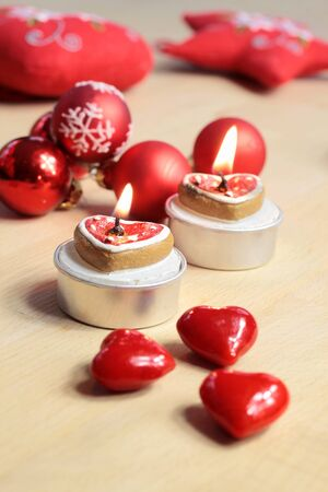 Burning candles in heart shape with Christmas balls and hearts photo