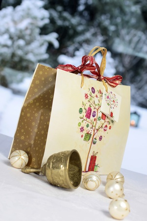 Golden Christmas bell, Christmas balls and gift bag in front of snow covered terrace Stock Photo - 15885002