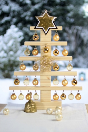 Home-made wooden Christmas tree in front of snow covered terrace Stock Photo - 15885056