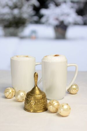 Golden Christmas bell, Christmas balls and gift bag in front of snow covered terrace photo