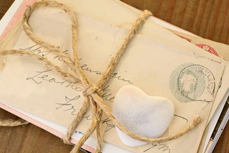 love proof: Stone heart with old tied letters on wooden desk