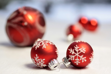 Small red Christmas balls on a white table cloth
