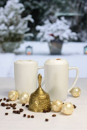 Golden Christmas bell and coffee cups, Christmas balls and coffee beans in front of winter terrace Stock Photo - 16605151