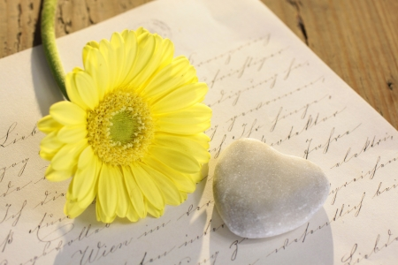 Stone heart with old letter and yellow flower Stock Photo - 16709746